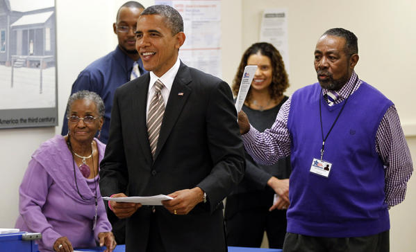 President Barack Obama greets election officials as he visits Chicago to vote early in the Bronzeville neighborhood on Thursday.