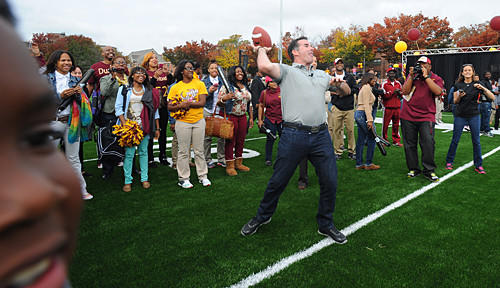 Under Armour founder and CEO Kevin Plank, center, prepares to throw a pass on Dunbar's new football field.