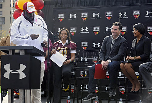 Dunbar football coach Lawrence Smith, left, presents the school's back-to-back championship ring to Under Armour founder and CEO Kevin Plank, second right, during the news conference to unveil the school's new field.
