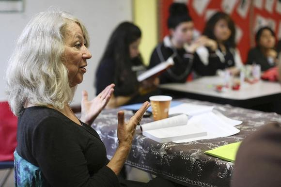 Karen Thomson, left, reads and discusses a book with a group of high school teenagers.