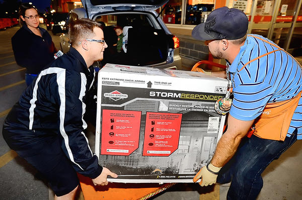 Paul Sommerfeld of Maugansville, left, gets a hand loading a power generator into his car from Home Depot Lot Associate Chris Diaz Friday night. Sommerfeld purchased the last generator in stock from the Home Depot in Hagerstown.