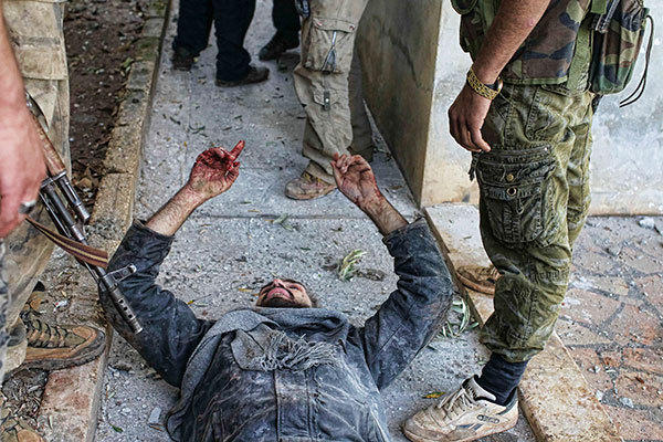 A wounded man, suspected to be from pro-government forces, talks to members of the Free Syrian Army as he tries to convince them he did not participate in shooting at them during fighting and a combing operation in Haram town, Idlib Governorate, October 26, 2012. The Free Syrian Army is advancing over pro-government forces for control of the town.
