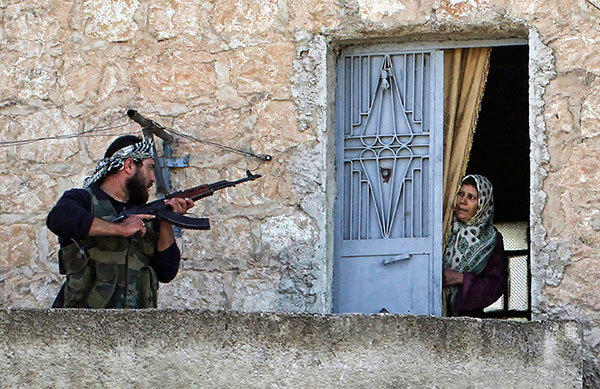 A member of the Free Syrian Army talks to a woman during a patrol to search for pro-government forces in Haram town, Idlib Governorate, October 26, 2012. The Free Syrian Army is advancing over pro-government forces for control of the town.
