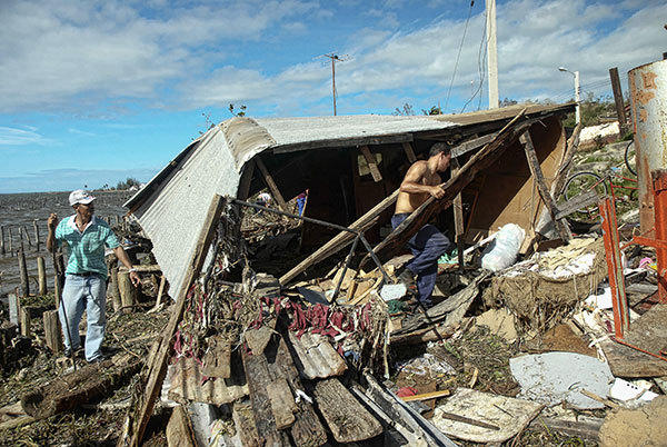 Cubans tries to recover belongings from a their destroyed house in Antillas population, Holguin province, 750km east of Havana, on October 26, 2012.  Hurricane Sandy claimed 11 lives as it tore across Cuba Thursday, leaving a path of destruction in the eastern part of the island, officials in Havana said.