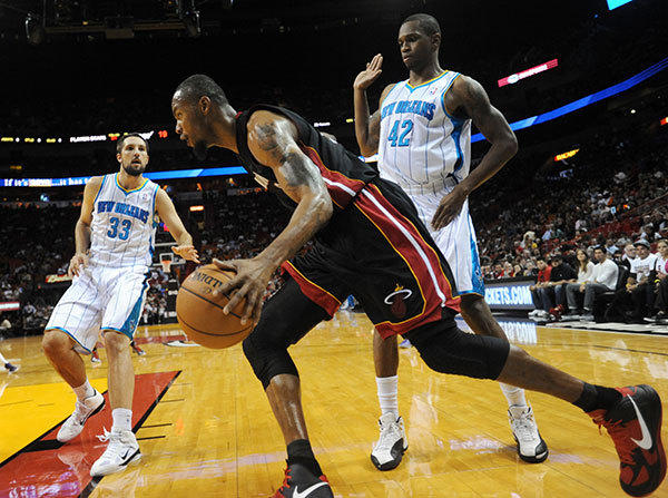Rashard Lewis of the Miami Heat drives past Lance Thomas (right0 of the New Orleans Hornets during a preseason game at the American Airlines Arena. Miami Heat vs. New Orleans Hornets.