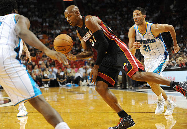Ray Allen of the Miami Heat looks to pass the ball after driving by Greivis Vasquez of the New Orleans Hornets during a preseason game at the American Airlines Arena. Miami Heat vs. New Orleans Hornets.