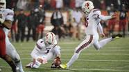 Louisville Cardinals quarterback Will Stein (4) holds the ball as kicker John Wallace (45) kicks the game winning field goal during overtime against Cincinnati Bearcats