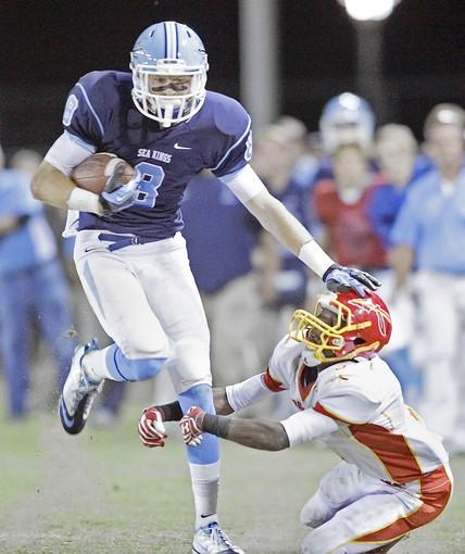 Corona del Mar High's Troy Reese (8) fends off Woodbridge's James Carr.