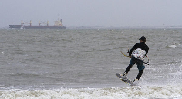 Andrew Hyatt of Newport News kiteboards at Buckroe Beach on Saturday afternoon as wind and rain picked up ahead of Hurricane Sandy.