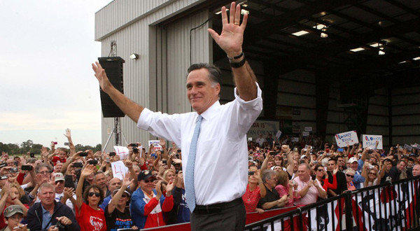 Republican presidential candidate Mitt Romney responds to cheering supporters at an airport rally in Kissimmee, Fla.