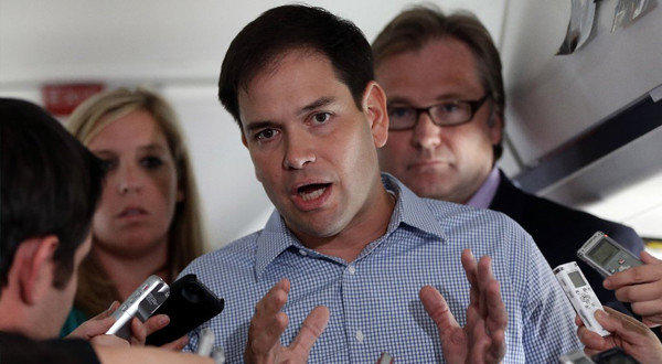 Sen. Marco Rubio (R-Fla.) who is traveling with Republican presidential candidate Mitt Romney, speaks to reporters on Romney's campaign plane en route to Orlando, Fla.
