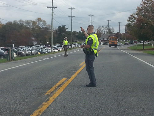 A Harford County deputy sheriff and Maryland state trooper direct traffic on Route 1 Saturday around one of the remote parking lots for this weekend's Zombie Run at Camp Ramblewood in Darlington.