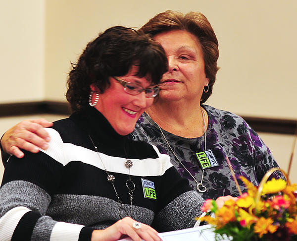 Transplant organ recipient Aleta Irving, right, hugs her donor Lisa Koontz after Koontz described their story Saturday at an organ donor symposium at Boonsboro American Legion.