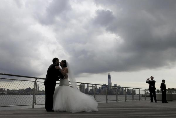 Newlyweds Kyle Legman (L) and Michelle Sheivachman (R) kiss as they pose for their wedding pictures under storm clouds, across from New York's Lower Manhattan in a park along the Hudson River in Hoboken, New Jersey,  October 27, 2012.