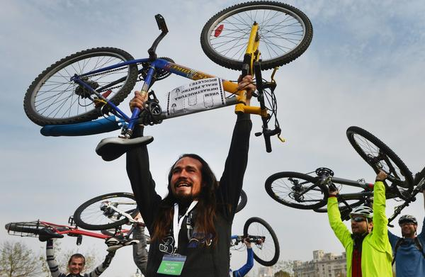 Romanians lift their bikes at the end of a march and protest in Bucharest, on October 27, 2012. Over 500 cyclist take part in a march demanding the right to a coherent infrastructure for cycling as Bucharest still not has on-road bike tracks.