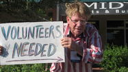 "Brian Baker, a volunteer for the Obama campaign, stood outside the Obama campaign headquarters on Sistrunk Boulevard on Saturday, waving his ""volunteers needed'' sign to traffic headed to early voting at the African-American Research Library and Cultural Center."