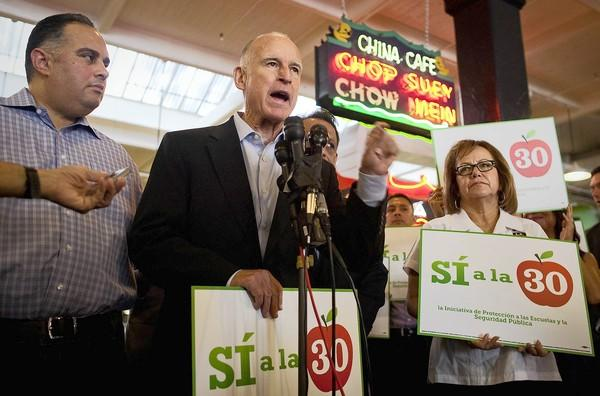 Standing between Assembly Speaker John Perez, left, and Maria Elena Durazo of the L.A. County Federation of Labor, Gov. Jerry Brown campaigns for his Proposition 30 at Grand Central Market in downtown Los Angeles.