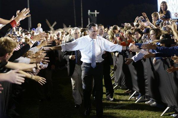 Mitt Romney reaches out to supporters as he campaigns on the football field at Land O'Lakes High School in Land O'Lakes, Fla.