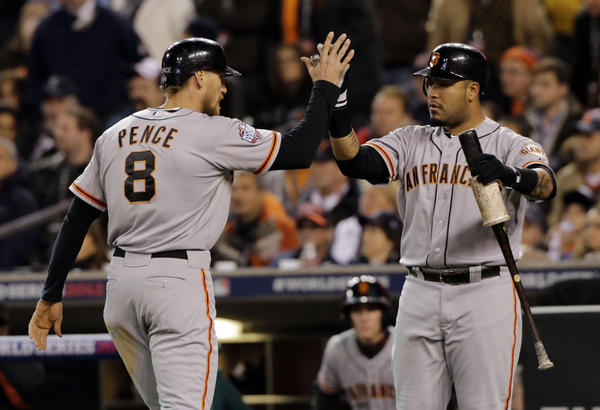 Hunter Pence high-fives Hector Sanchez after scoring on a triple by Gregor Blanco in the second inning of Game 3.