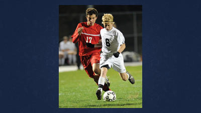 The Indians' Ben Wilson (6) moves the ball up field against Rockwood's John Knox (17) in high school soccer playoff action Saturday night in Davidsville.