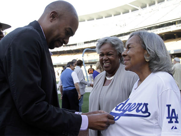 Sharon Robinson looks on as her son, Jesse, helps Rachel Robinson, Jackies widow, with a jersey at Dodger Stadium in May. Sharon will join the Dodgers' board of directors before next season.