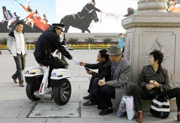A Chinese police officer checks the identity of men resting in Beijing's Tiananmen Square. Authorities have heightened security ahead of next month's Communist Party congress.