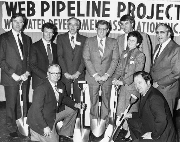 Dignitaries gathered at Selby High School on Oct. 28, 1982, for a ground-breaking ceremony for WEB Water. They are, from left to right, standing, Sen. Larry Pressler, Congressman Tom Daschle, WEB Chairman Morris Kurle, Gov. Bill Janklow, U.S. Department of Interior Assistant Secretary Garrey Carruthers, Mrs. Clint Roberts, Sen. James Abdnor. Front left, kneeling: John Sieh, Oahe Subdistrict chairman, and Joe Marcotte, Bureau of Reclamation regional director.