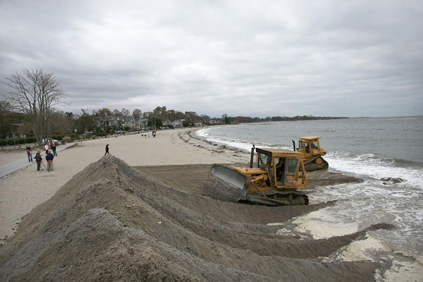 Earth movers build protective berms on Compo Beach as the first signs of Hurricane Sandy approach in Westport, Conn.