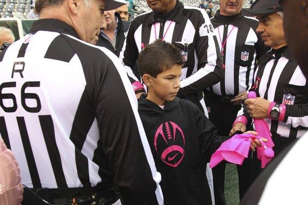 Dante Cano meets with game officials and gets a look at the pink penalty flags to be used in the Jets-Dolphins game today at MetLife Stadium.