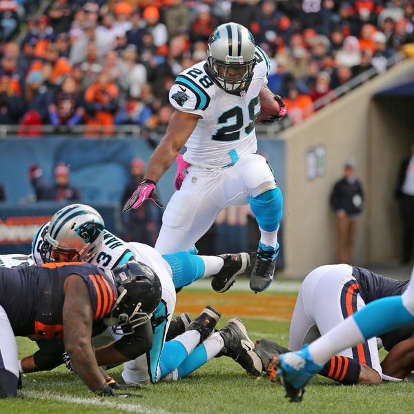 Panthers running back Jonathan Stewart jumps over defensive tackle Henry Melton for a carry during the first quarter.