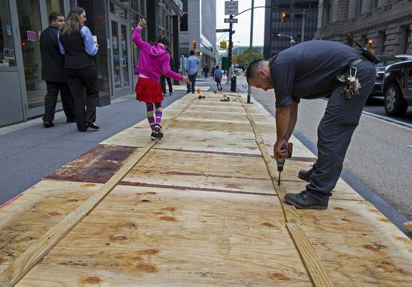 A worker puts plywood over sidewalk grates in Lower Manhattan as Wall Street prepares for Hurricane Sandy.
