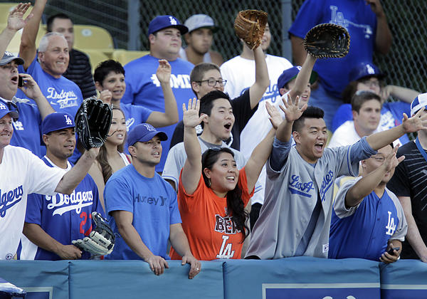 "A Giants fan wearing an orange ""Beat LA"" T-shirt joins a crowd of Dodgers fans in left field trying to catch balls hit during batting practice at Chavez Ravine."