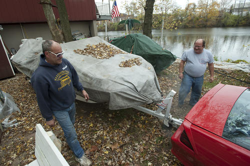 Adams Island resident Marshall Peifer of Allentown (left) gets help from friend Joe Martin of Allentown tow his boat to higher ground after receiving a evacuation notice on Sunday around 2 PM. Weather forecasters warned Lehigh Valley residents will feel the effects of Hurricane Sandy long before the eye of the storm comes ashore sometime Monday night.