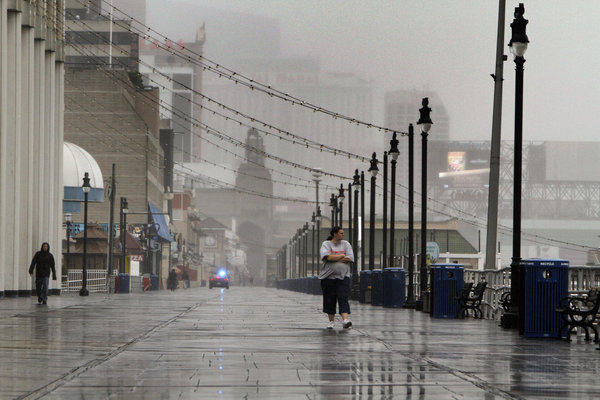People walk along the Atlantic City Boardwalk in Atlantic City, N.J., as the area prepares for Hurricane Sandy.