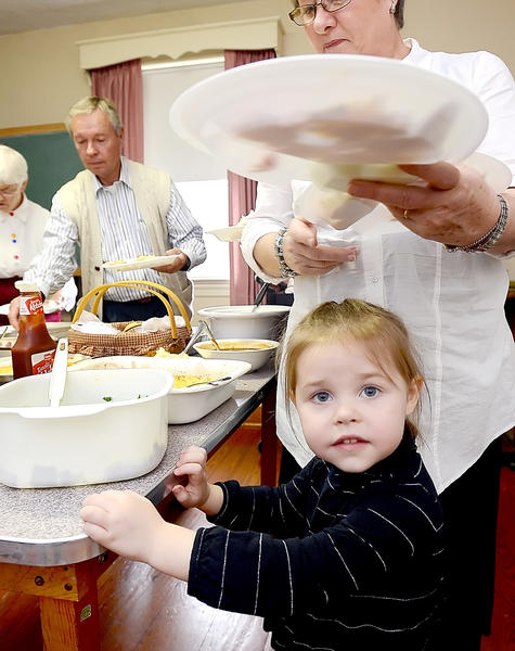 Sloane Dunn, 2, of Fairplay waits for her grandmother, Lynda Matheny, to fill her plate Sunday as the Downsville Church of the Brethren celebrated its 155th anniversay.