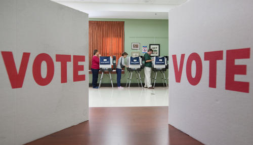 Voters cast their ballots electronically in the background as two cardboard voting partitions are seen on a table in the foreground used for those who need to fill out ballots on paper.