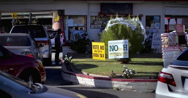 """No on Measure H"" signs are planted in the lawn near a burger drive-through in El Monte. Mayor Andre Quintero thought residents would back the penny-per-ounce tax on sugar-filled drinks because of the city's financial woes and high rates of childhood obesity. But the beverage industry has spent more than a million dollars on its campaign against the measure. Supporters of the measure have spent $57,000."