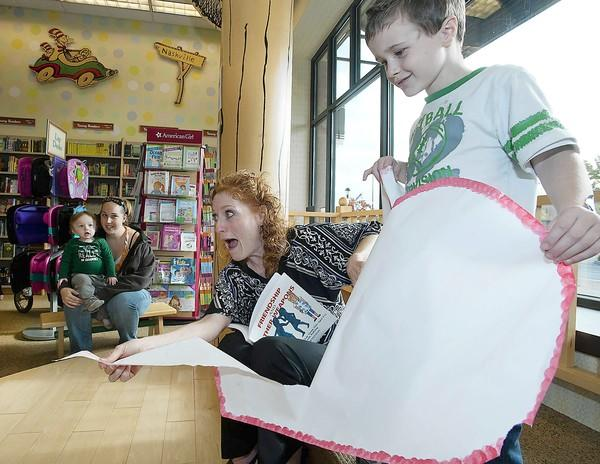 Joey Todd, 5, (right) holds a paper heart as South Whitehall author Signe Whitson reads her book 'Friendship & Other Weapons' to children at the Barnes & Noble bookstore at the Promenade Shops at Center Valley.