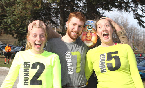 A friendly zombie grab has (from left) German exchange student Laura Stahmer, Tom Rich of Dexter, costume-wearing Ron Freed and Elise Freed of Boyne City laughing, as they prepare to start the Zombie Mountain Attack 5k at Avalanche Preserve in Boyne City. The second annual fundraiser benefits the Boyne City High School cross country and robotics teams.