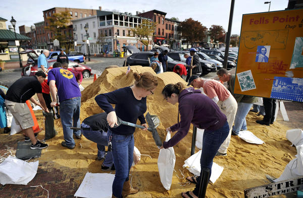 Foreground, left to right, Katie Keane, Fells Point, and Alaina Graves, Canton, fill bags with sand to protect their homes from Hurricane Sandy. Keane lives a block and a half from the water.