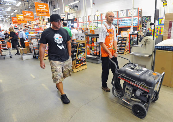 James Boyd, of Essex, left, bought the last gas generator at the Eastern Avenue Home Depot as Paint Department Supervisor Fred Jogerit, right, help roll the generator to the check out line. The store sold out of the over 50 generatorsit had in stock as Baltimore City and County residents pick up emergency supplies such as flash lights.
