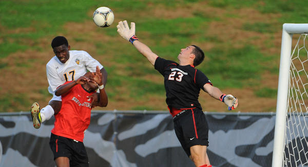 Northeastern goalie Oliver Blum (23) knocks the ball away in the last play of regulation time after Towson's Olakunle Banjo (17) tried to head the ball in.