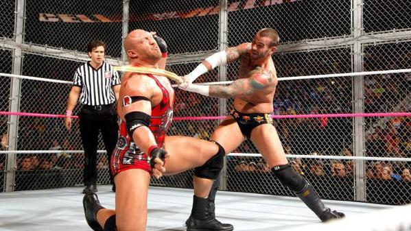 WWE champion CM Punk uses a kendo stick across the chest of Ryback as referee Brad Maddox looks on.