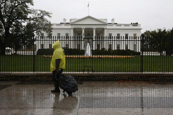 A man wearing a rain pouch walks past the White House in Washington during the approach of Hurricane Sandy. The nation's capital was largely deserted as the federal government and most businesses shut down.