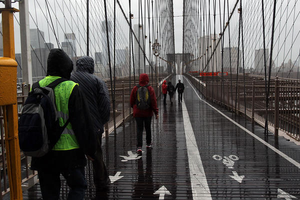 People walk across the Brooklyn Bridge as Hurricane Sandy begins to affect the area in New York City. The storm, which threatens 50 million people in the eastern third of the U.S., is expected to bring days of rain, high winds and possibly heavy snow. New York Governor Andrew Cuomo announced the closure of all New York City will  bus, subway and commuter rail service as of Sunday evening.