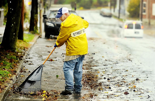 A worker with the Williamsport Streets Department clears leaves away from the aide of Artizan Street on Monday morning to prevent clogged drains from expected heavy rainfall from Hurricane Sandyd.