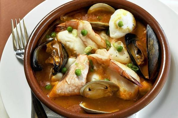 Casuela de Mariscos is a Mediterranean seafood stew featuring fish, scallops, calamari and mussels over roasted potatoes in a seafood sauce.