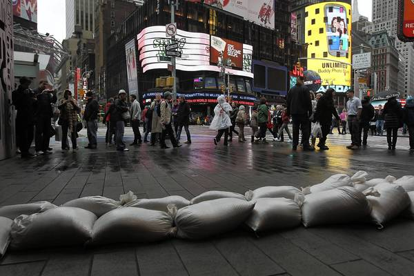 Photos: Hurricane Sandy: People walk by sand bags in front of a building in Times Square as Hurricane Sandy begins to affect New York City. The storm, which threatens 50 million people in the eastern third of the U.S., is expected to bring days of rain, high winds and possibly heavy snow. New York Governor Andrew Cuomo announced the closure of all New York City will bus, subway and commuter rail service as of Sunday evening.