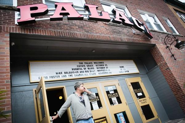 David Bacchiochi makes a phone call outside his newly opened Palace Theater on Main Street in Stafford.,
