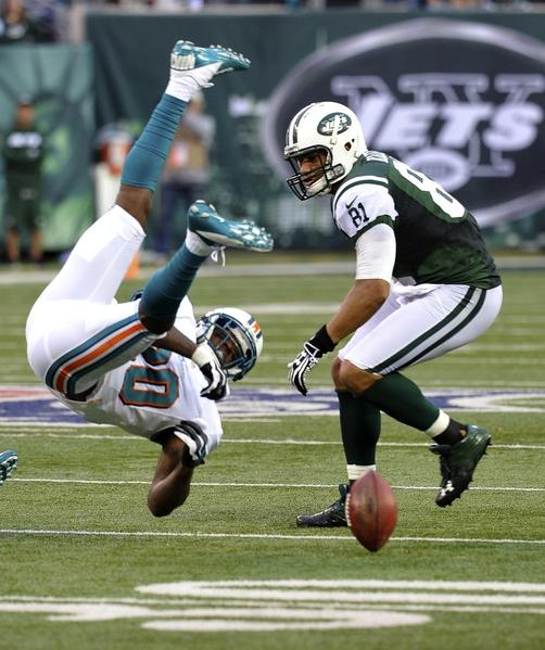 Miami Dolphins Reshad Jones (L) flips upside down after failing to intercept a pass thrown to New York Jets Dustin Keller (R) in the third quarter during their NFL football game in East Rutherford, New Jersey, October 28, 2012.